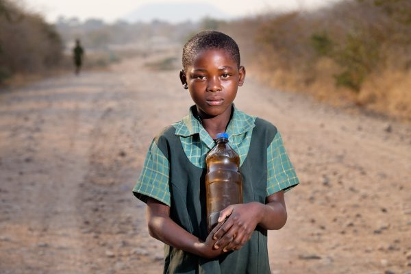 Girl (10y.) on the road from Gokwe to Gokwe North. She takes water to school in an empty plastic beer bottle. The water comes from a well and is unsafe. People don't boil the water before drinking because it is time consumming and there is not enough wood (expensive).